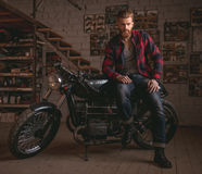 Guy in motorbike repair shop. Handsome bearded man in stylish casual clothes is posing at camera while sitting on the motorcycle in the repair shop Royalty Free Stock Photos