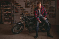 Guy in motorbike repair shop. Handsome bearded man in stylish casual clothes is sitting on the motorcycle in the repair shop Royalty Free Stock Image