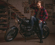 Guy in motorbike repair shop. Handsome bearded man in stylish casual clothes is sitting on the motorcycle in the repair shop Stock Photo