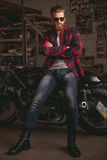 Guy in motorbike repair shop. Handsome bearded man in stylish casual clothes and sun glasses is posing at camera while leaning on the motorcycle in the repair Royalty Free Stock Images