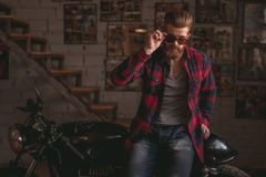 Guy in motorbike repair shop. Handsome bearded man in stylish casual clothes and sun glasses is posing at camera while sitting on the motorcycle in the repair Royalty Free Stock Photo