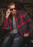 Guy in motorbike repair shop. Handsome bearded man in stylish casual clothes and sun glasses is posing at camera while sitting on the motorcycle in the repair Royalty Free Stock Images