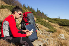 The guy in the mountains, hike with a backpack, and a solar pane. Royalty Free Stock Image