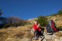 The guy in the mountains, hike with a backpack, and a solar pane. Stock Photos
