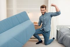 The guy moves the sofa while moving to a new home. The guy does a reshuffle in the room. Stock Photography