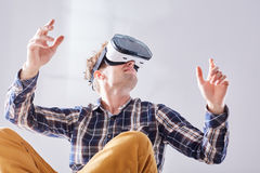 Guy moves to future with VR glasses. Young guy sits with crossed legs and moves to future with VR glasses Royalty Free Stock Photography