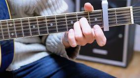 Guy Musician Plays uma guitarra acústica com um Capo filme