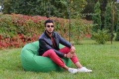 Guy Musingly Looks Aside árabe e sorrisos, resto e assento dentro foto de stock