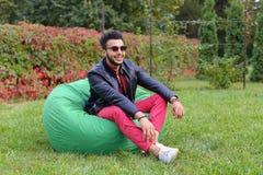Guy Musingly Looks Aside árabe e sorrisos, resto e assento dentro fotografia de stock royalty free