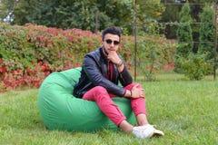 Guy Musingly Looks Aside árabe e sorrisos, resto e assento dentro imagens de stock royalty free