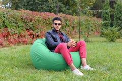 Guy Musingly Looks Aside árabe e sorrisos, resto e assento dentro imagens de stock