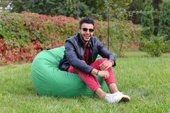 Guy Musingly Looks Aside árabe e sorrisos, resto e assento dentro fotos de stock