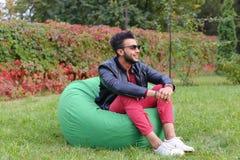 Guy Musingly Looks Aside árabe e sorrisos, resto e assento dentro fotografia de stock