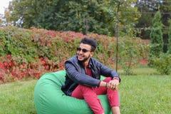 Guy Musingly Looks Aside árabe y sonrisas, resto y el asistir Foto de archivo