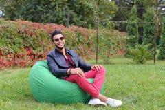 Guy Musingly Looks Aside árabe y sonrisas, resto y el sentarse Imagen de archivo libre de regalías