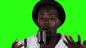 Guy with a mustache and beard sings into a retro microphone. Green screen. Slow motion. Close up stock footage