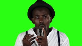 Guy with a mustache and beard wearing a hat and sunglasses sings into a retro microphone. Green screen. Slow motion stock footage