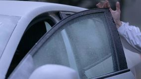 A guy in national costume places accordion inside of his icy car stock footage