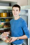 Guy  near opened refrigerator in kitchen Stock Images