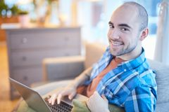 Guy networking. Young man in casualwear relaxing at leisure with laptop while searching in the net or watching webcast Royalty Free Stock Photography