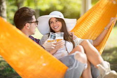 Guy and nice girl drink beer in hammock Stock Photo