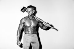 Guy with a nice muscle fitness, bodybuilder hold big metal hammer. Athlete and hammer. guy with a nice muscle fitness, bodybuilder hold big metal hammer Stock Photography
