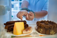 Guy at night has diet crisis and desire to eat sausages Stock Image