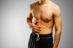 The guy with no shirt holding hand of the patient side. Stomach. Hurts. Pain in the liver royalty free stock images