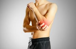 The guy with no shirt holding hand sore elbow. The location of t. He pain marked in red Royalty Free Stock Images