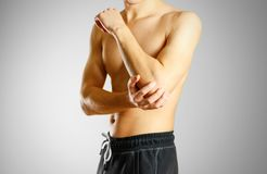 The guy with no shirt holding hand sore elbow. O grey background Royalty Free Stock Image