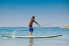 The guy with an oar on a surfboard. The beautiful brawny guy with an oar in hands on a surfboard Stock Photo