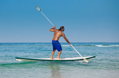 The guy with an oar on a surfboard. The beautiful brawny guy with an oar in hands on a surfboard Stock Image