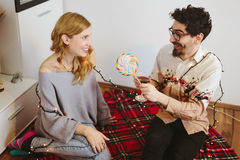 Guy offering a lollipop to a girl at home Stock Image