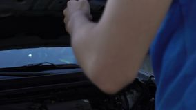 Guy opening hood of car and looks helpless, engine overheating issue, insurance