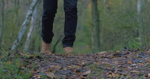 A guy in an orange jacket, boots and jeans walks through the autumn forest to the camera stock video footage
