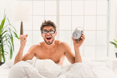 Guy outsleeping and looking at clock with fear Stock Images
