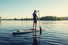 Free Guy Paddling On A SUP Board On Large River Royalty Free Stock Photos - 121119818