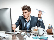 Guy with paper plane in his hand typing on a computer keyboard. Modern office man at working place, sloth and laziness concept Stock Photo