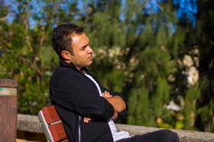 Guy on a park bench. Guy siting on a park bench with a contemplative expression in his face Stock Image