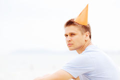 Guy in party hat on beach closeup Stock Images