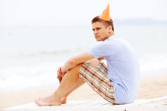 Guy in party hat on beach Royalty Free Stock Photography