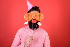 Guy in party hat celebrate, posing with photo props. Hipster in giant sunglasses celebrating. Emotional diversity. Concept. Man with beard on cheerful face stock image