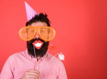 Guy in party hat celebrate, posing with photo props. Hipster in giant sunglasses celebrating. Man with beard on cheerful. Face holds smiling lips on sticks, red Royalty Free Stock Images