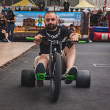 Guy pedalling on tricycle at Rocking the Park event in Milan, Italy Stock Images