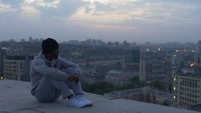 Guy pensively sitting on edge of skyscraper thinking about life, evening mist. Stock footage stock video footage
