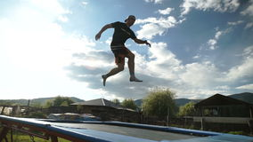 Guy performs acrobatic jumping on a trampoline against a background of mountains and blue sky. Outdoor summer stock footage