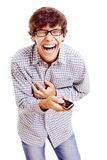 Guy with phone shrieking with laughter. Young latin man in black glasses and mobile phone in his hand doubling up with laughter. Isolated on white background royalty free stock photos