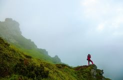 The guy with photo camera is staying on the crag in the fog. stock image