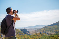 Guy photographing mountain in summer Stock Photos