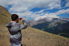 The guy photographs Elbrus. Height of the biggest top in Europe 5642 meters above sea level Stock Photos
